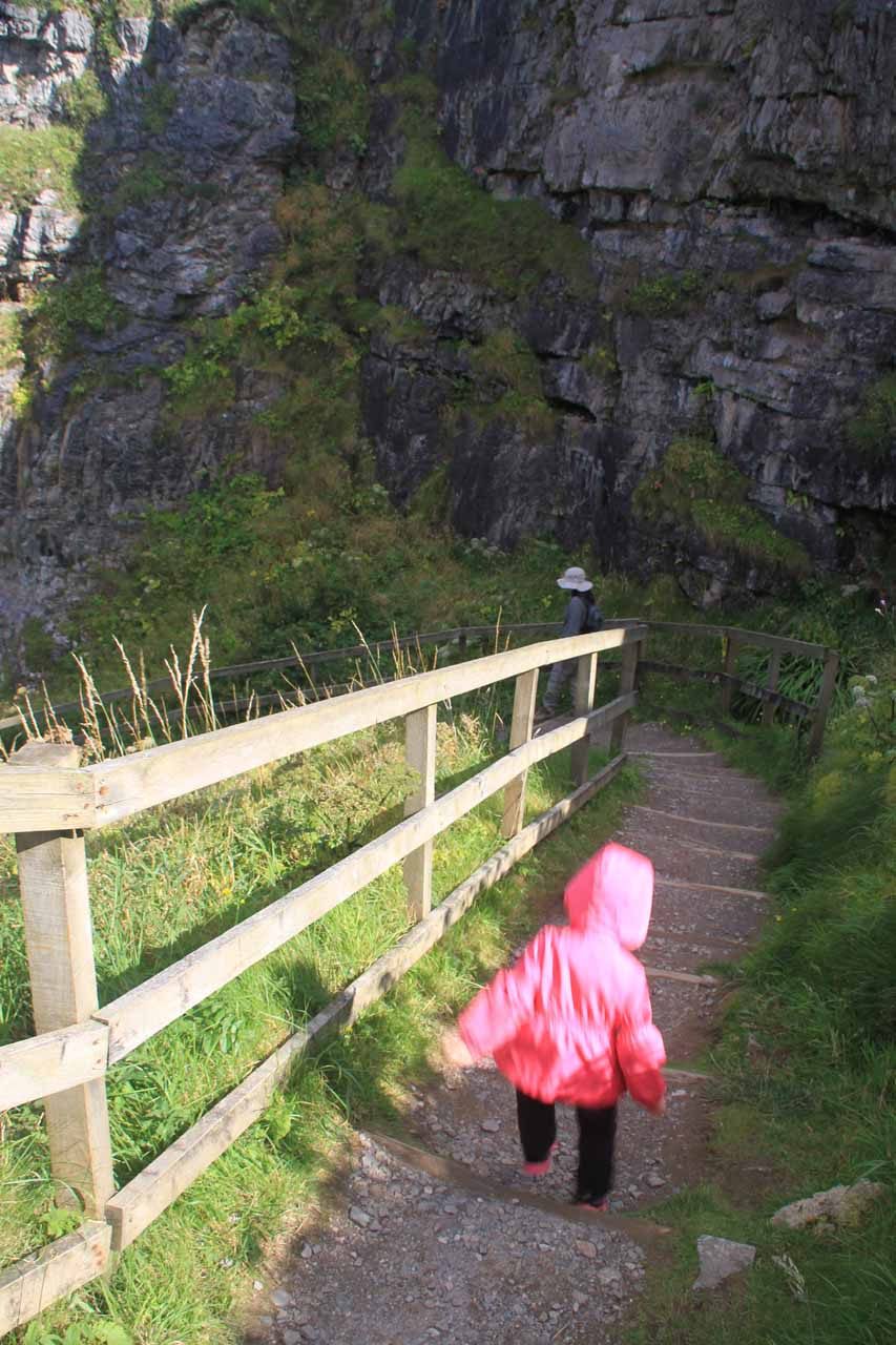 Tahia taking her time going down the steps to the entrance of the Smoo Cave below