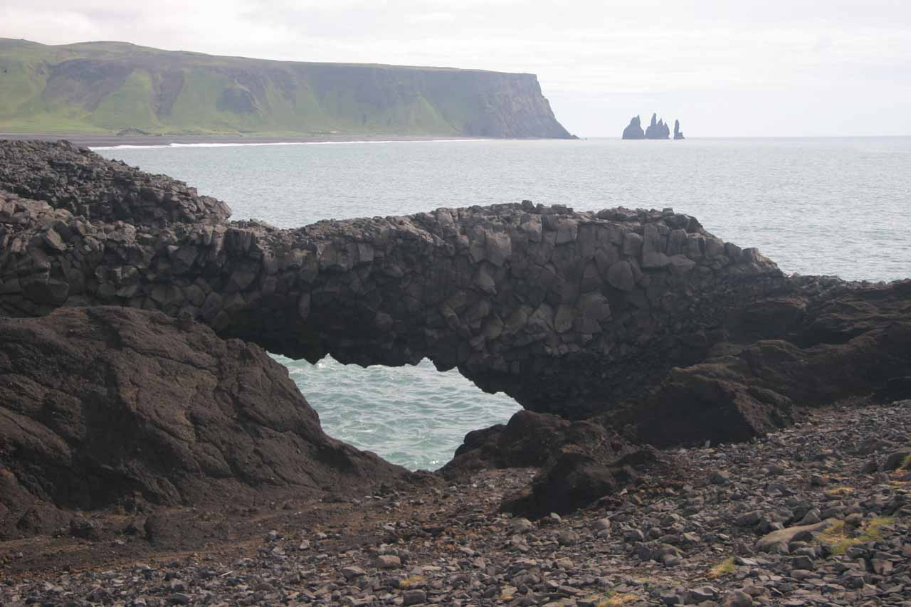 Our visit to Dyrhólaey surprised us with bonus arches like this thin lava arch backed by the Reynisdrangar in the distance