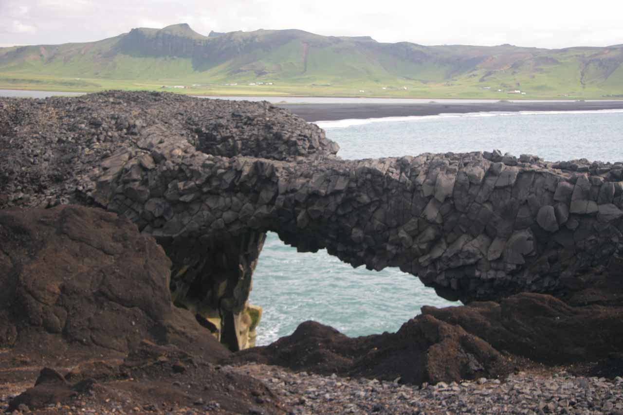 A natural arch and Reynisdrangar in the background