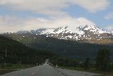 E6_southbound_drive_007_07072019 - Context of the E6 with snowy mountains higher up partially shrouded by clouds