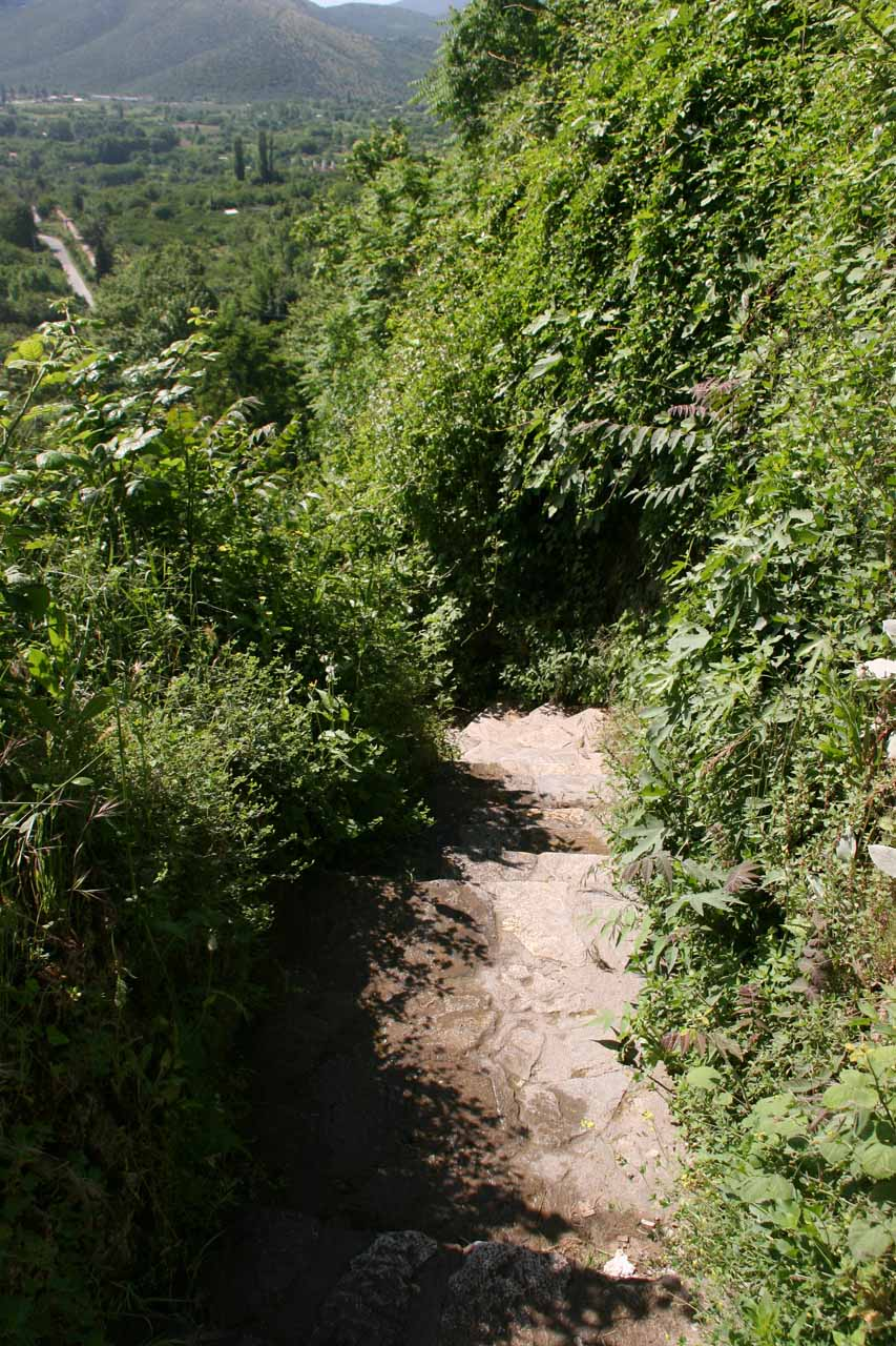 Looking down at the partially overgrown and slippery footpath leading further downstream of Karanos