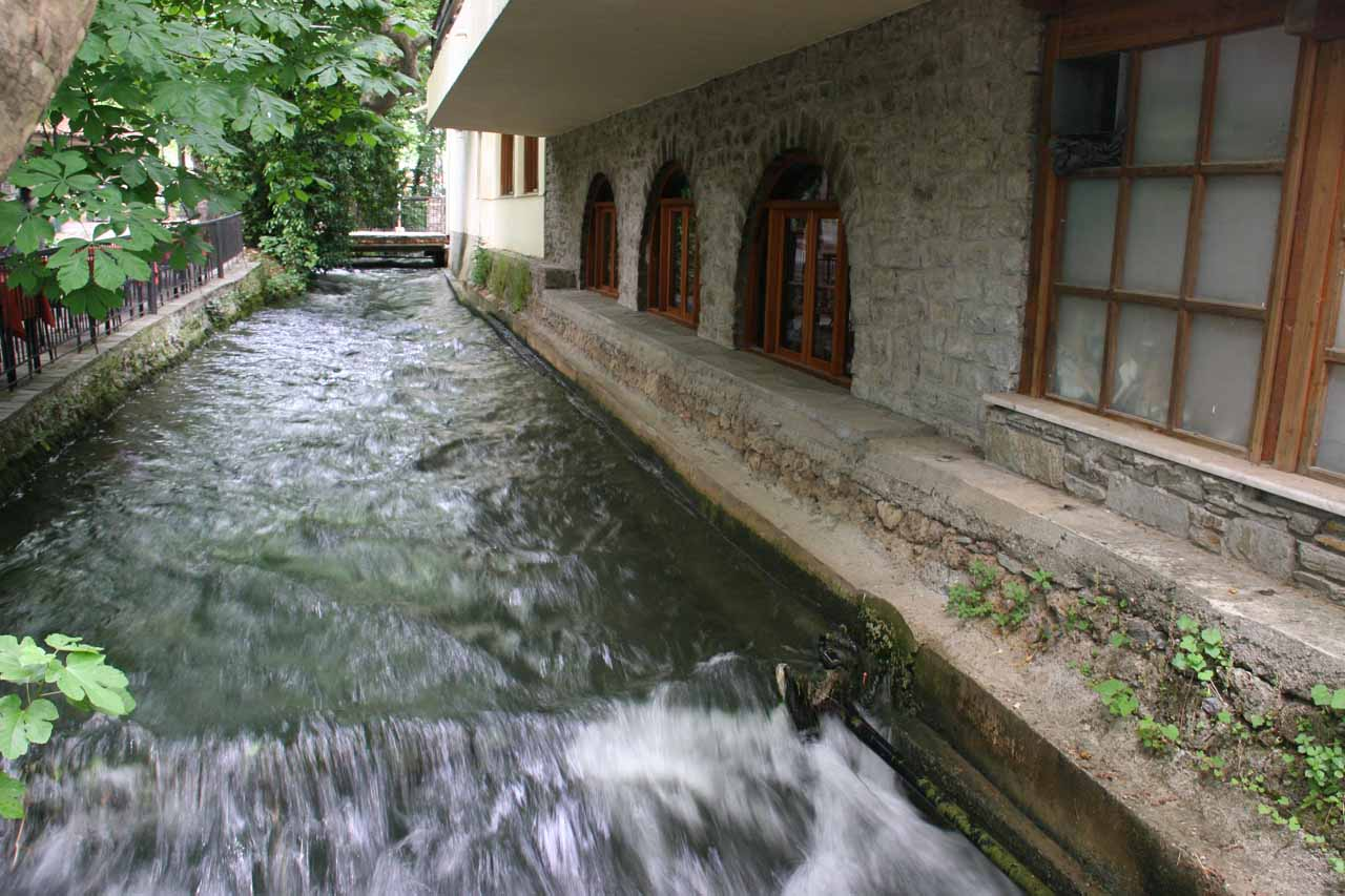 The stream literally wrapping around one of the buildings in the area right above the Edessa Waterfalls