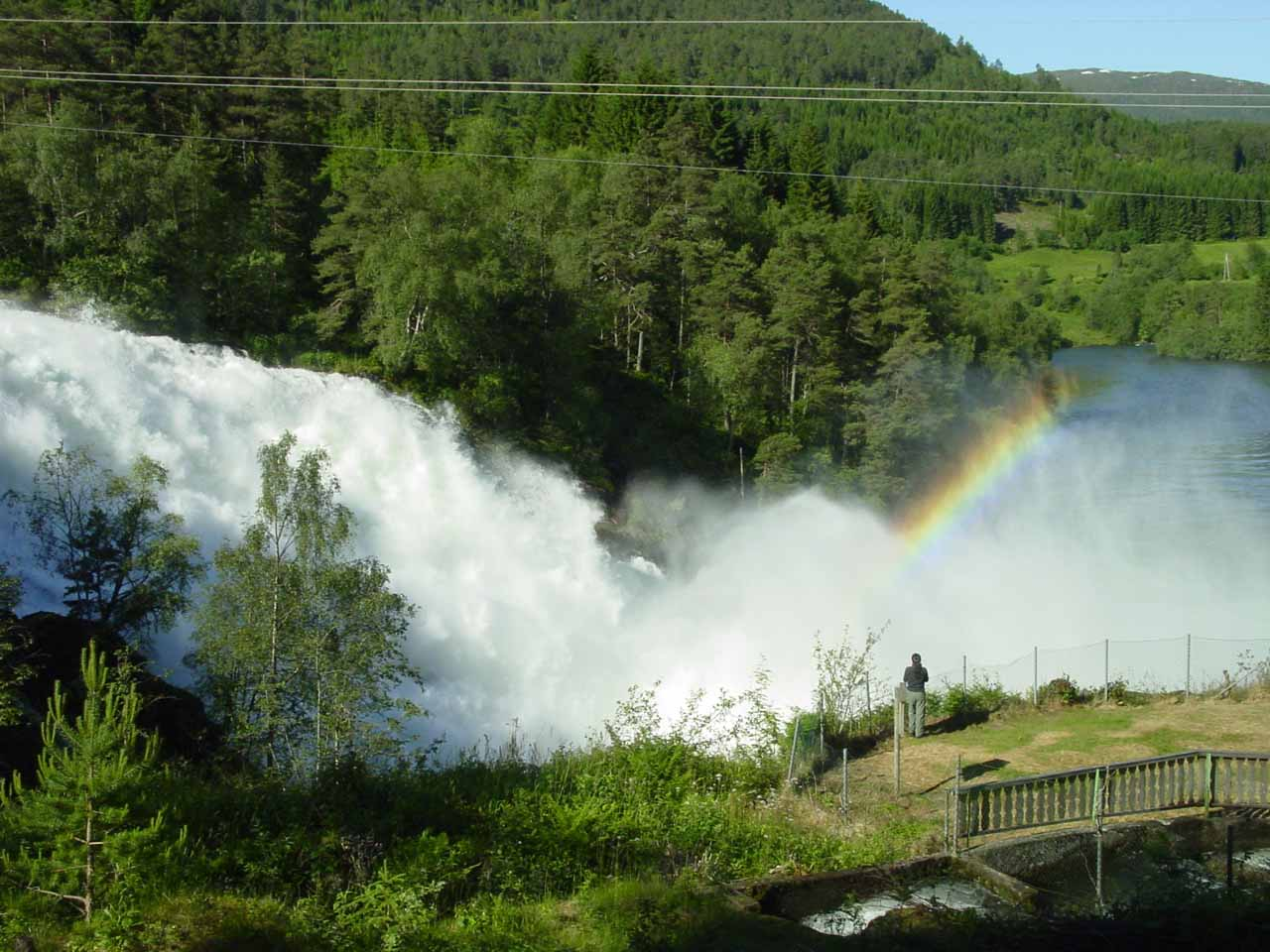 Looking down at Julie being dwarfed by both Eidsfossen and rainbow