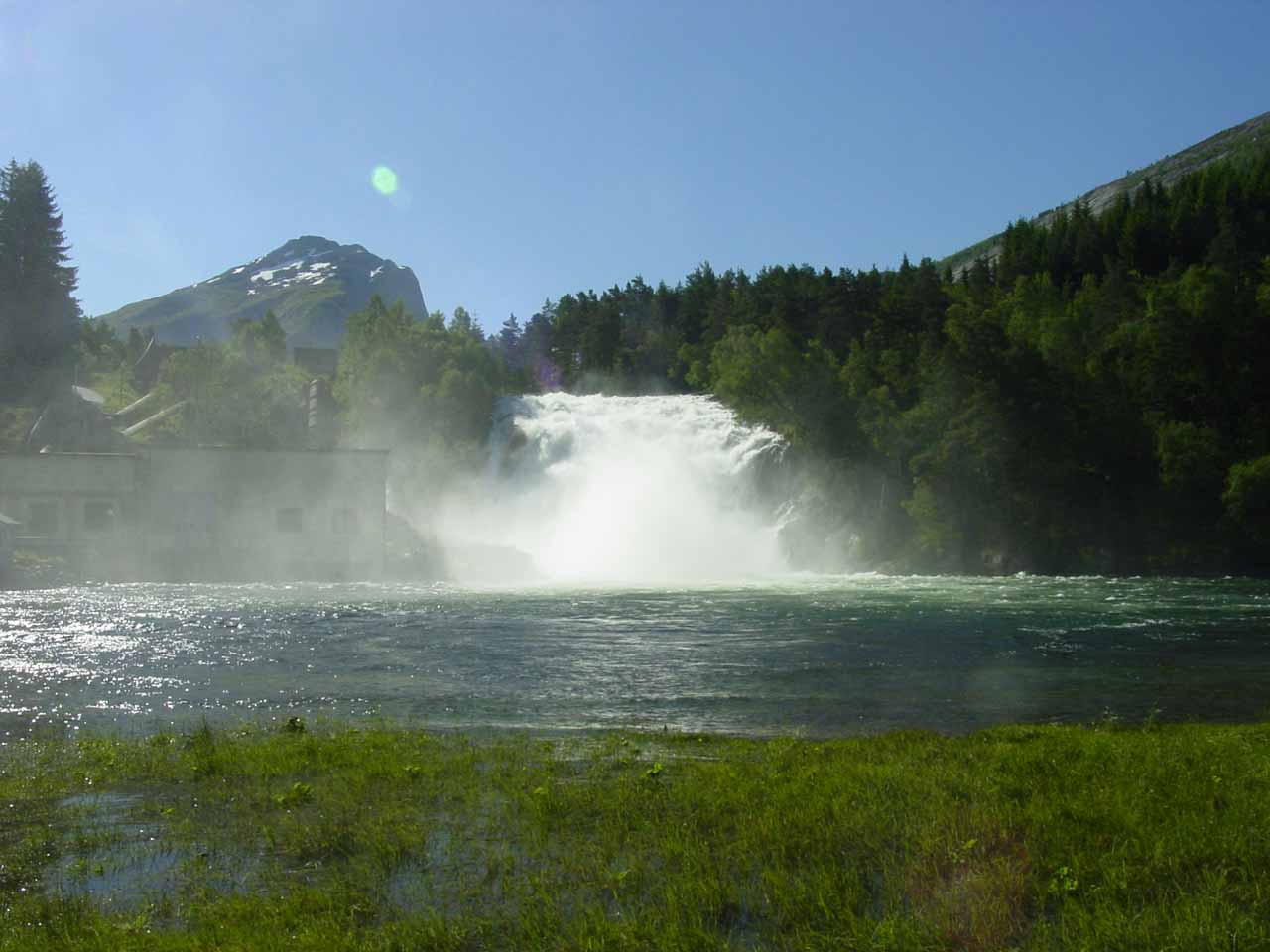 Looking directly at the base of Eidsfossen and the adjacent power station against both the spray and the morning sun