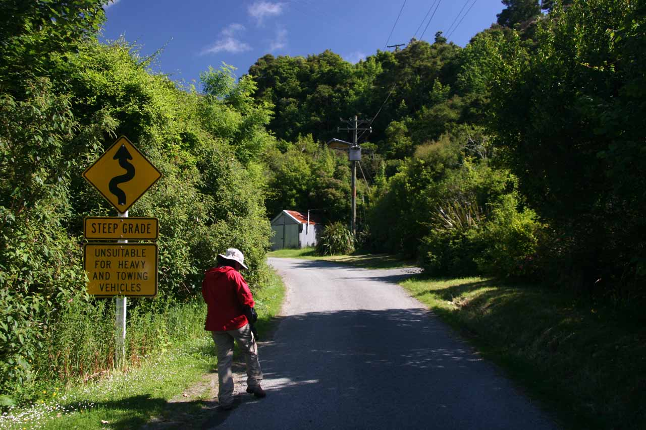 Julie starting the walk for Emily Falls as we passed by a sign warning us of the unsealed road's steep grade