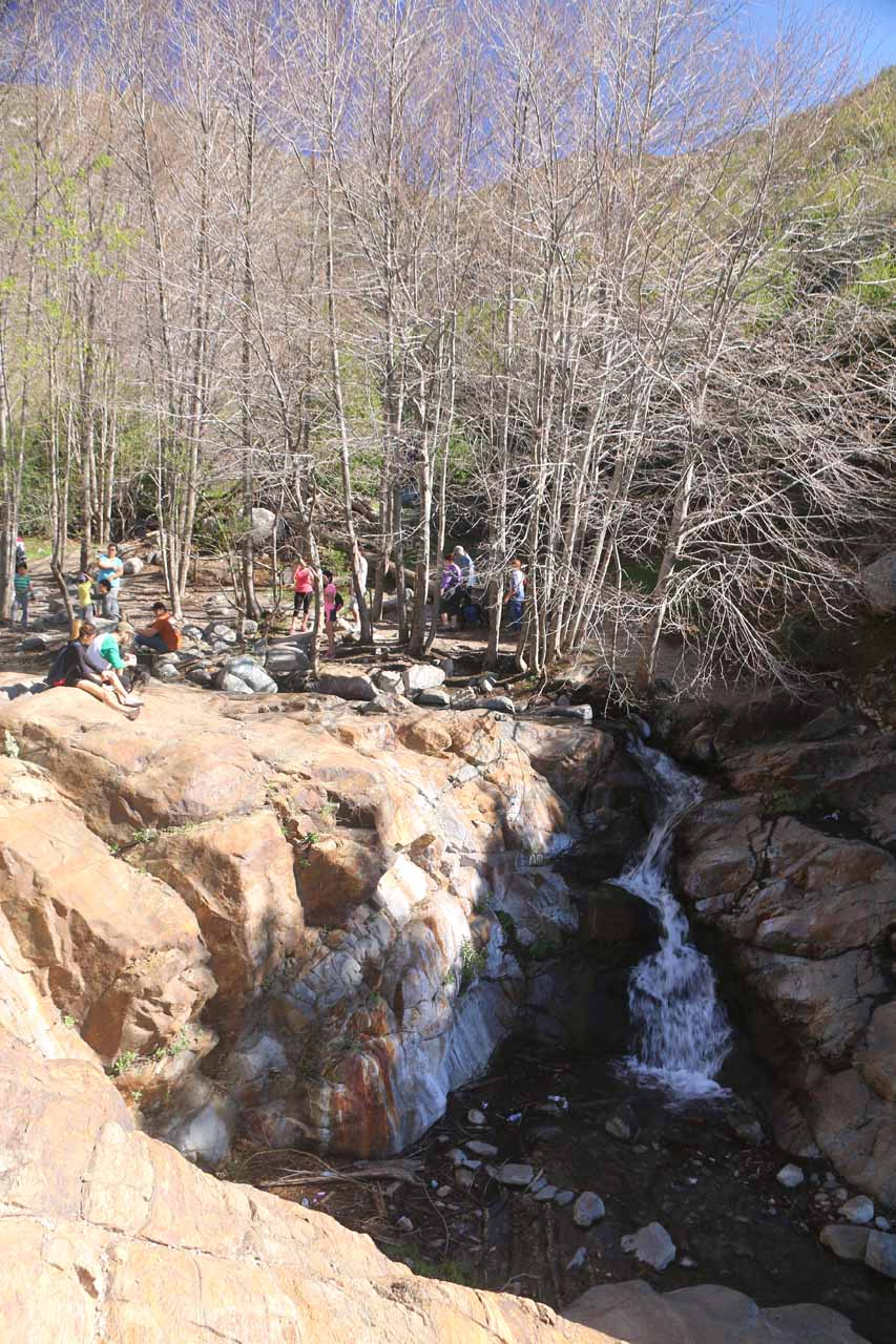 View of the context of the uppermost tier of Etiwanda Falls with lots of people playing in the stream above it