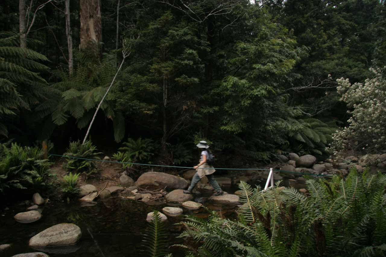 Julie going across a wide stream with boulders and a rope for balance