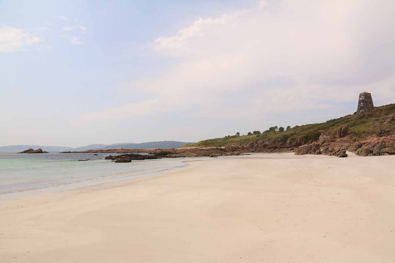 Looking along the white sands of the beach at Ezaro as well as the colorful waters of the Atlantic