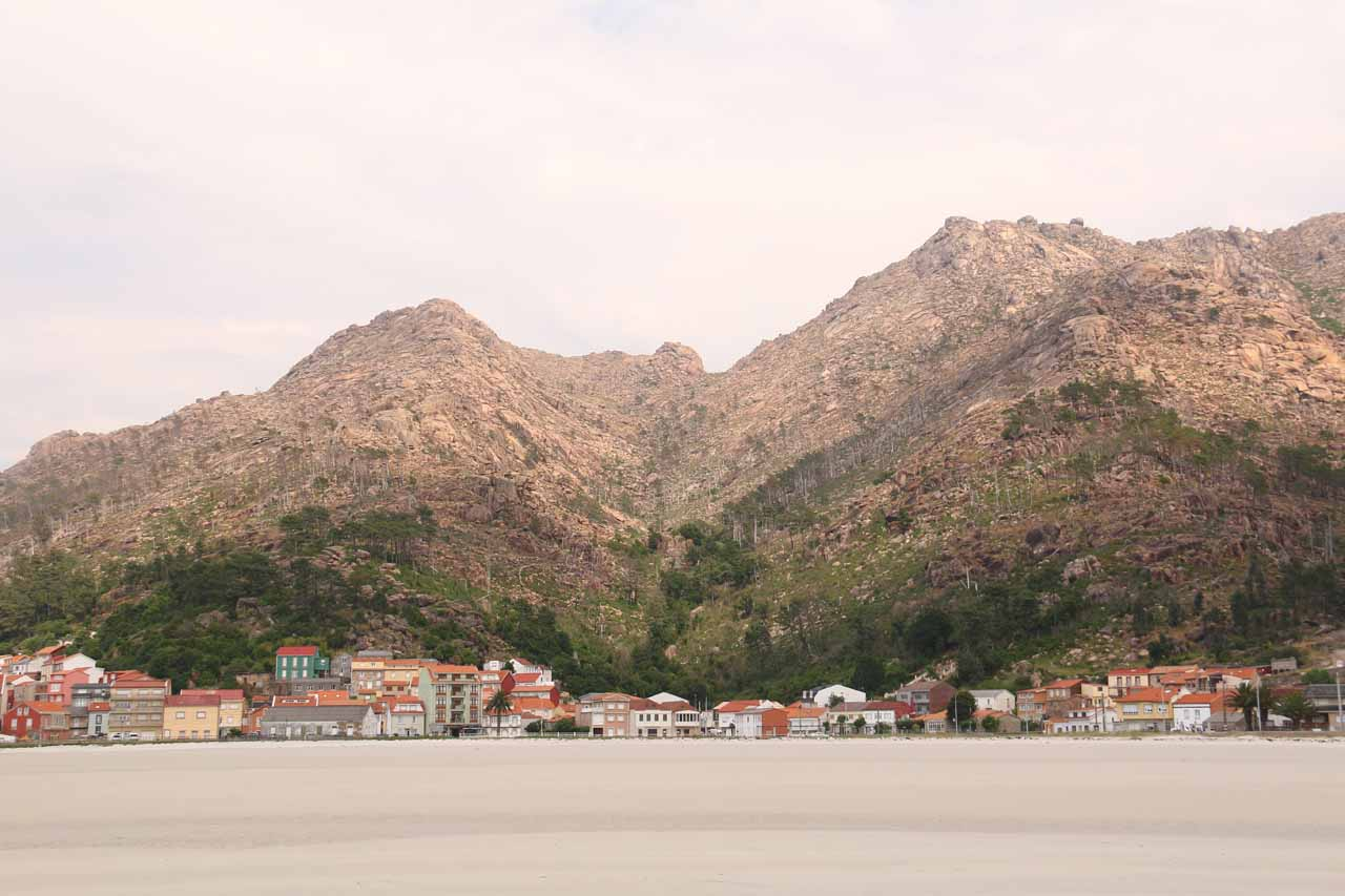 Contextual look back at Ezaro and the mountains backing it from near the water's edge at the beach