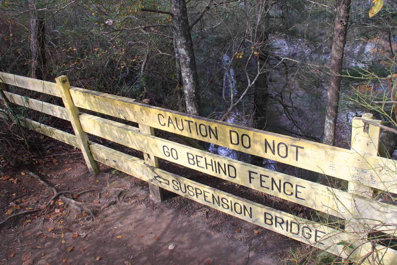 Yellow signage fronting an obstructed view of Piney Falls