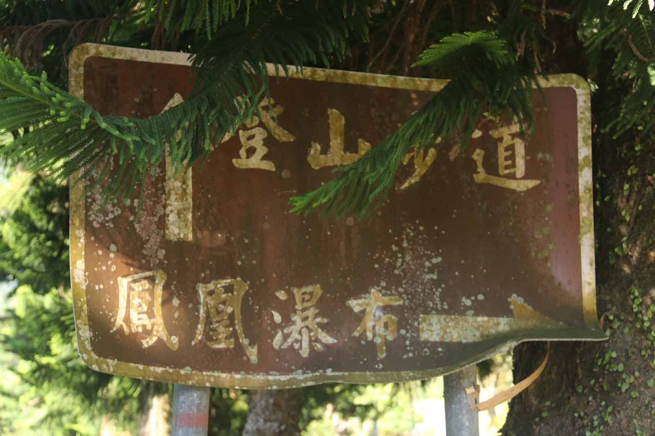 The faded brown sign pointing the way to our right for the Fenghuang Waterfall