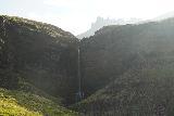 Flogufoss_041_08092021 - Direct look against the afternoon sun at Flögufoss, its natural bridge, and the Smátindar Peaks
