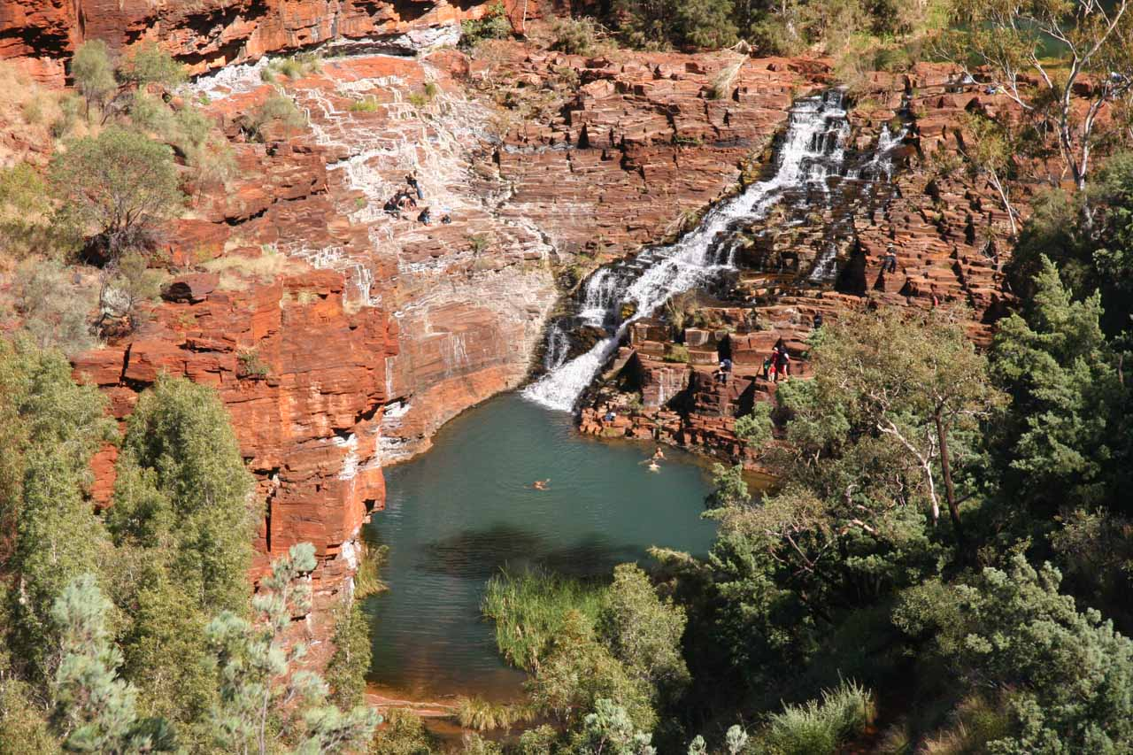 Contextual view of Fortescue Falls and its plunge pool surrounded by the bright red rock Dales Gorge