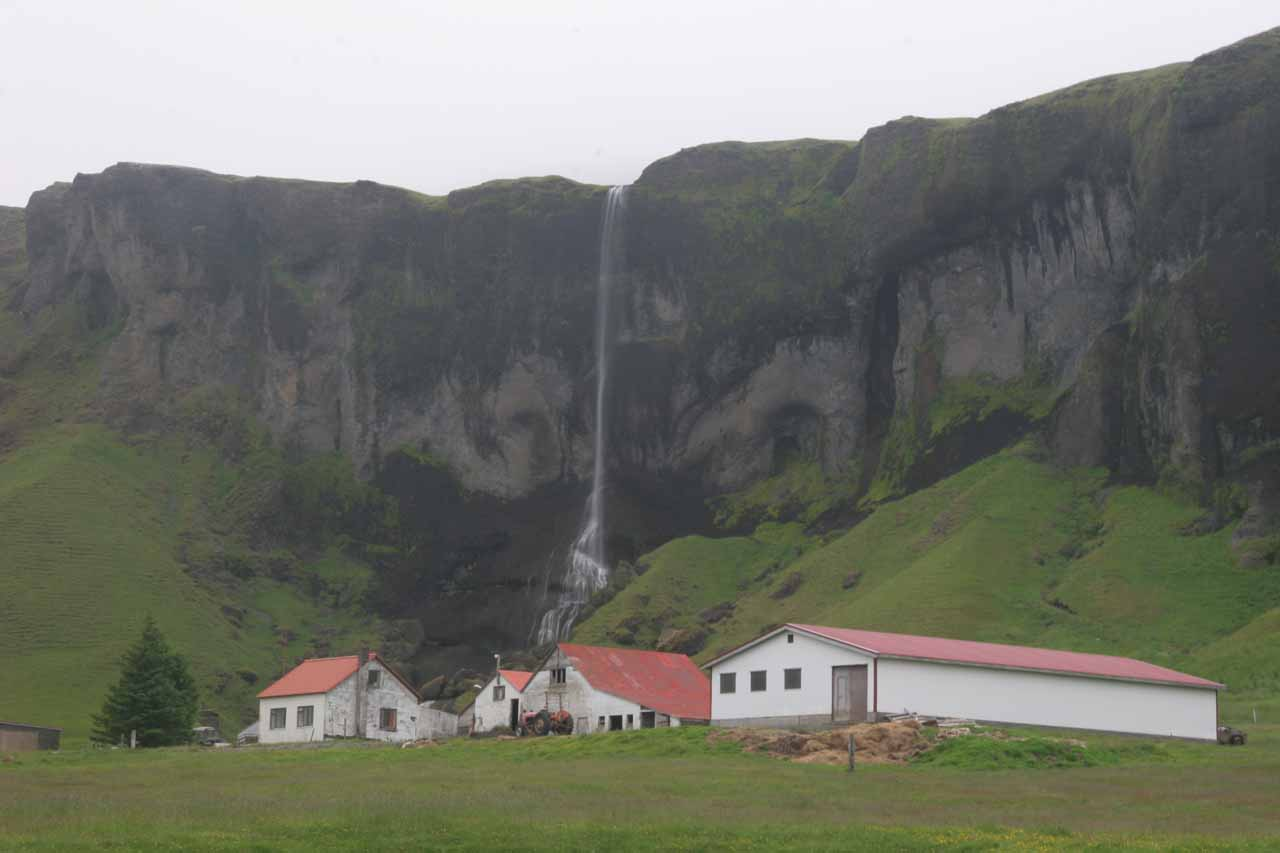 Looking directly at Foss a Sidu fronted by several farm buildings