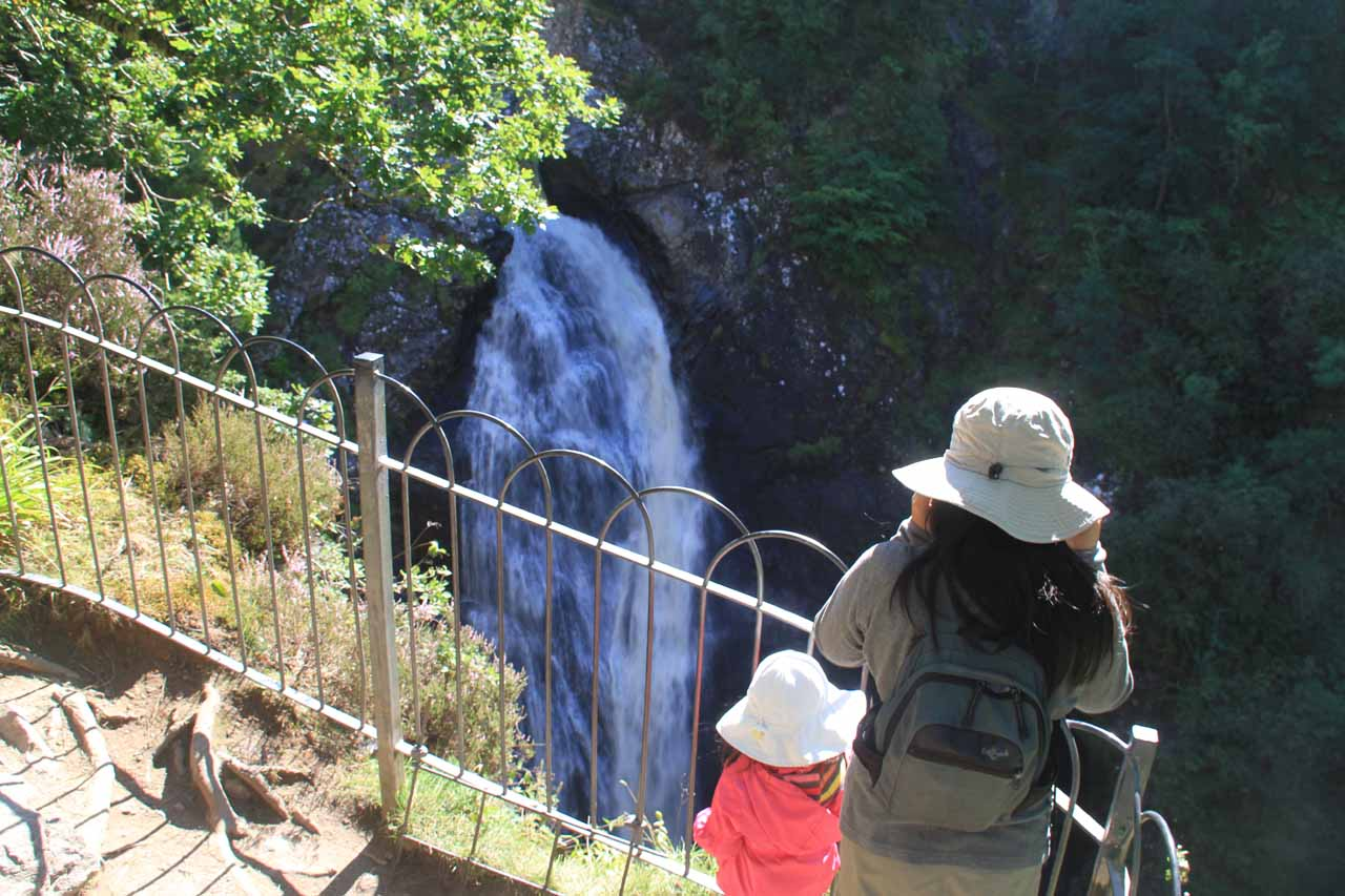 Julie and Tahia looking against the sun at the waterfall