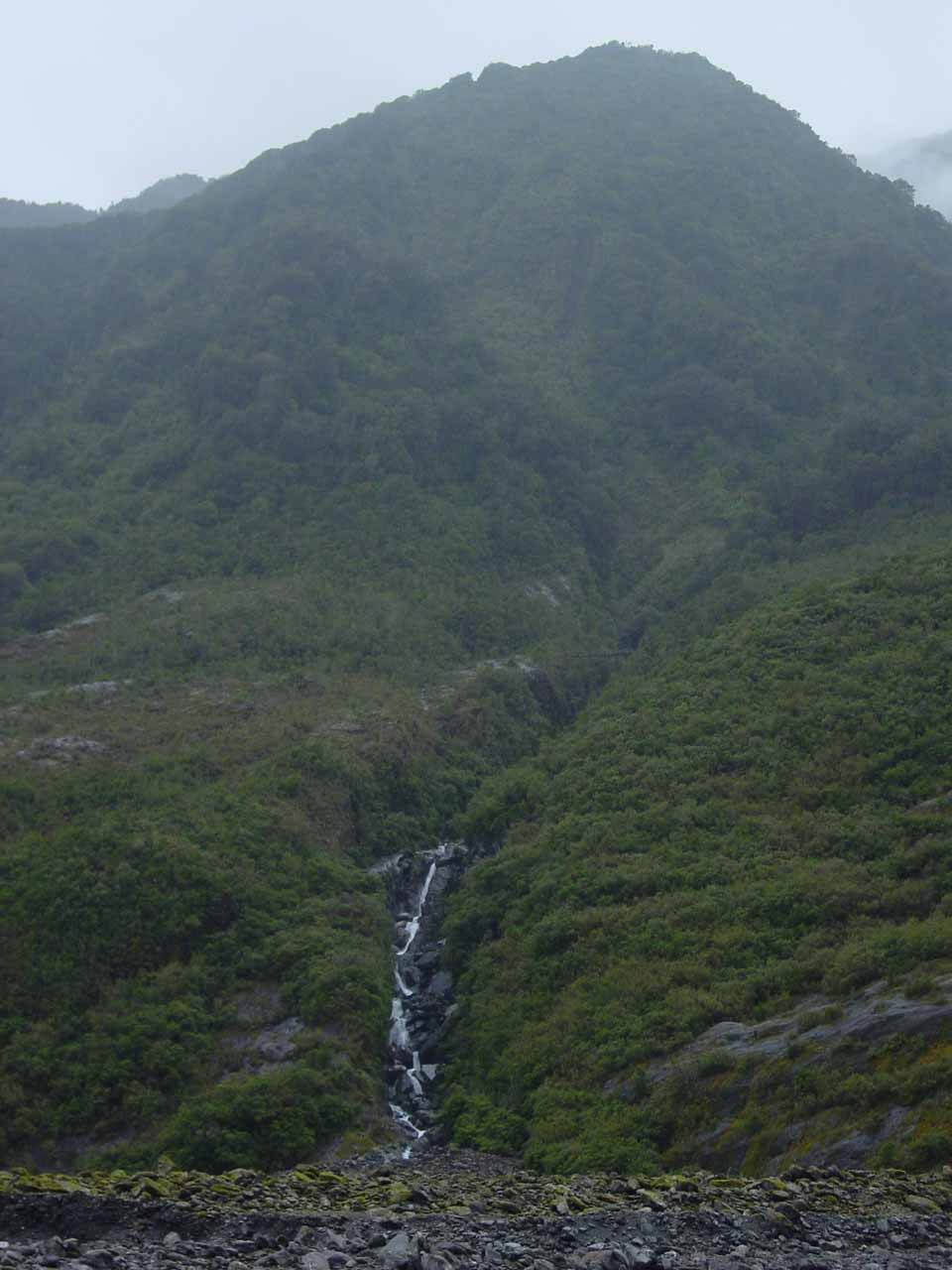 Looking across the valley towards this waterfall towered over by a bush-clad mountain