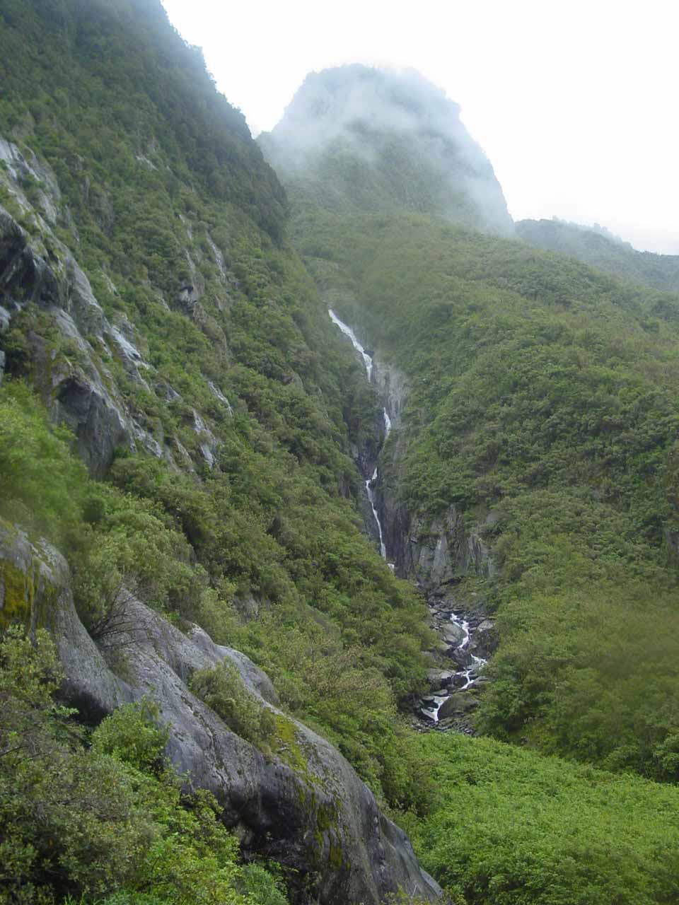 Another waterfall tumbling in a nook beneath a knobby mountain