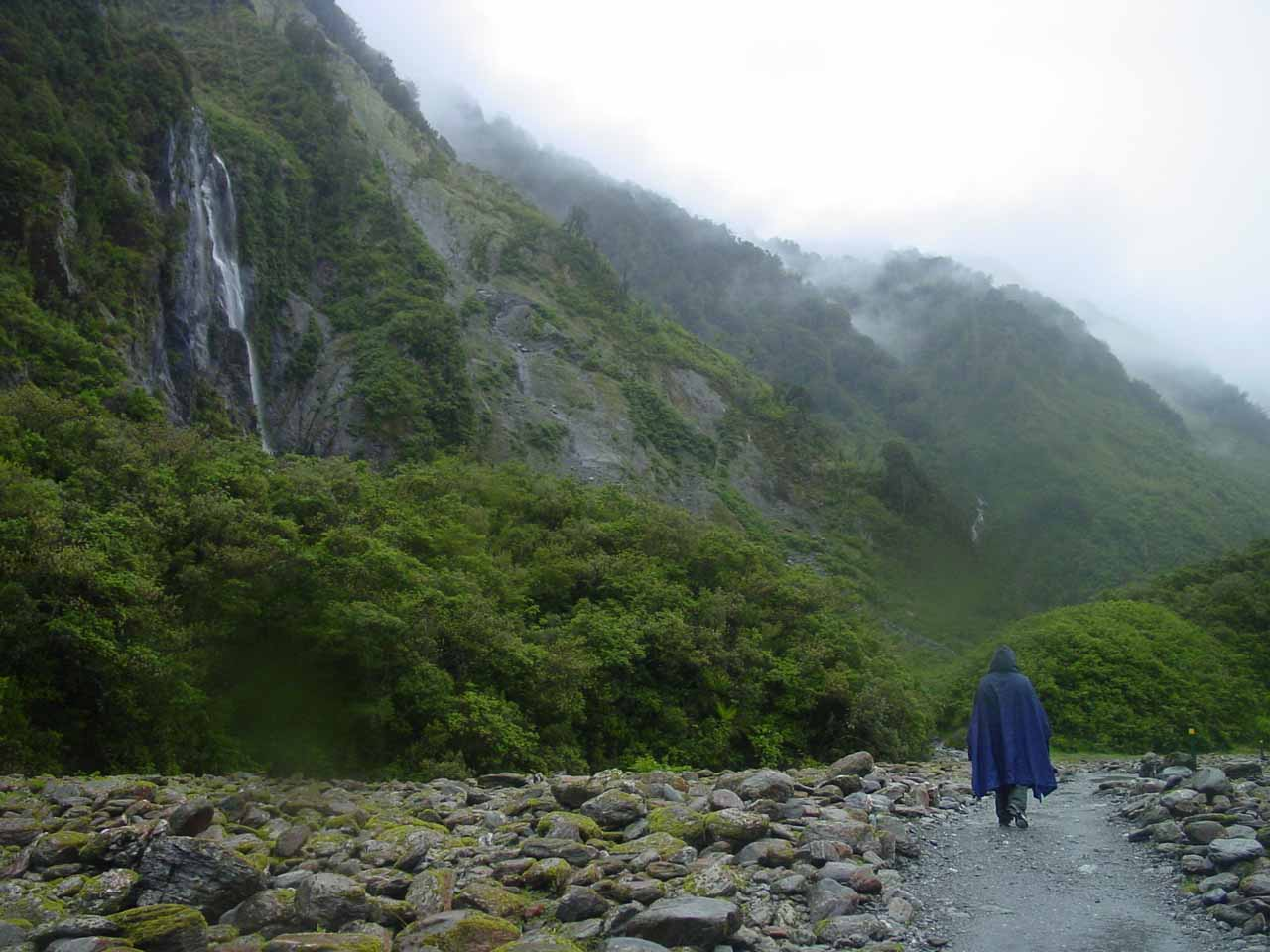 Walking in the rain under rejuvenated waterfalls at the Franz Josef Glacier in New Zealand