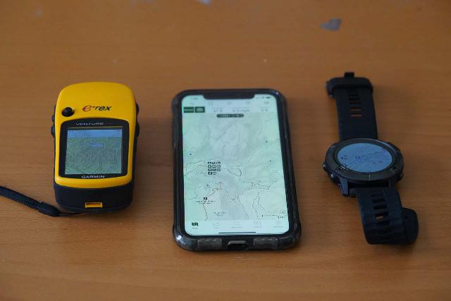The Garmin Fenix 6X Pro Sapphire compared against my old Garmin etrex Venture HC unit (left) and an iPhone loaded with Gaia GPS (middle)