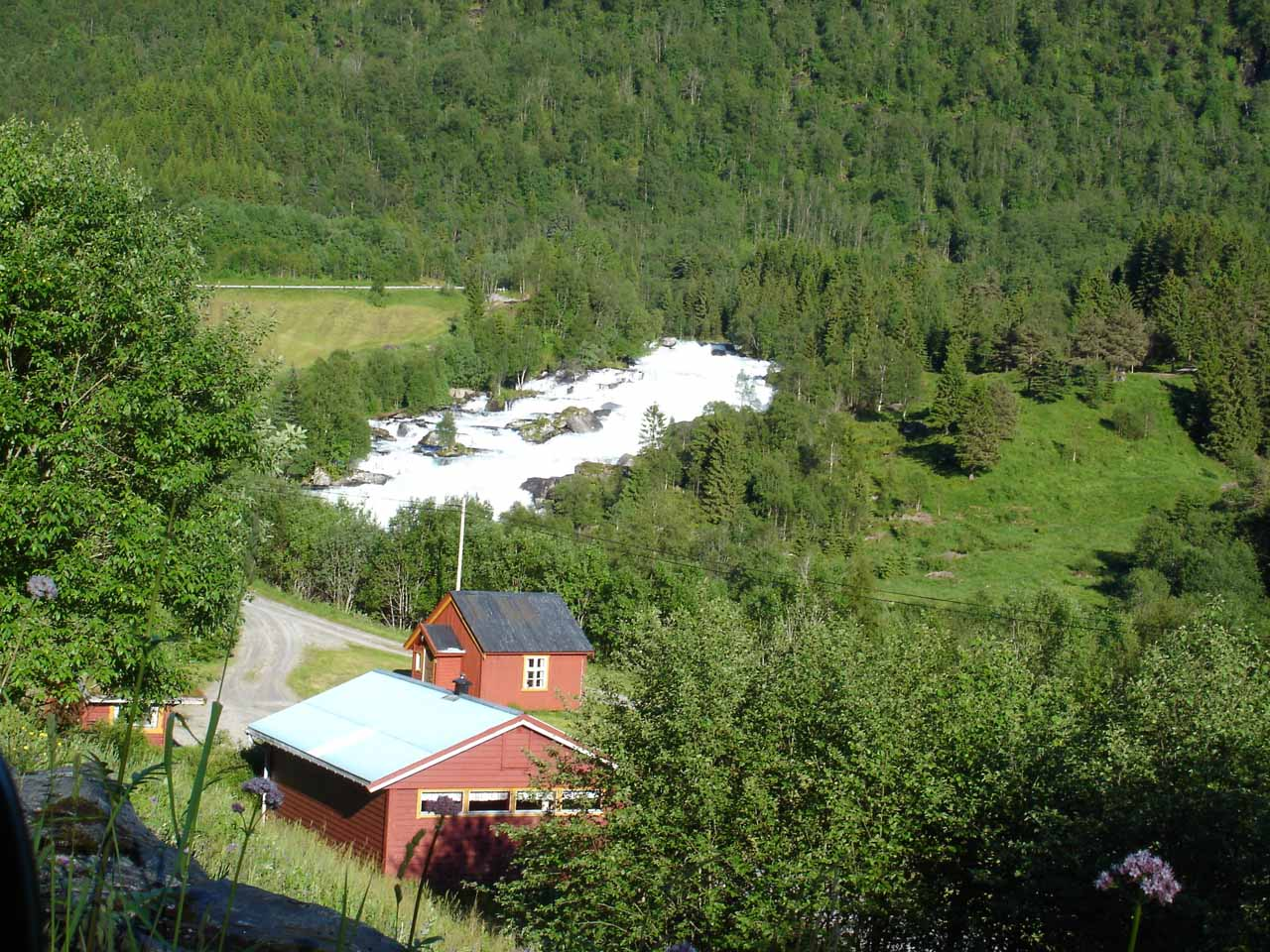 Some long and bright rapids fronted by farms that I think might be one view of Vallestadfossen