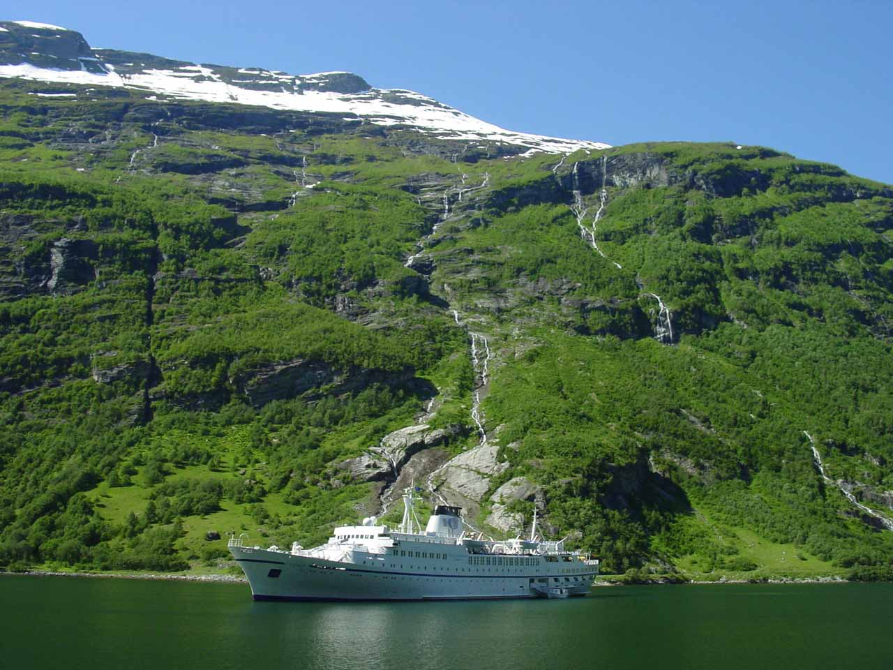 Many thin waterfalls seen tumbling behind one of the cruise ships on the Geirangerfjord