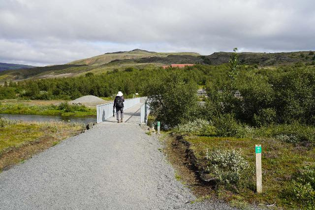Gjain_002_08202021 - Mom leaving the car park and about to traverse the Rauðá over a sturdy footbridge with the red-roofed Stöng in the distance