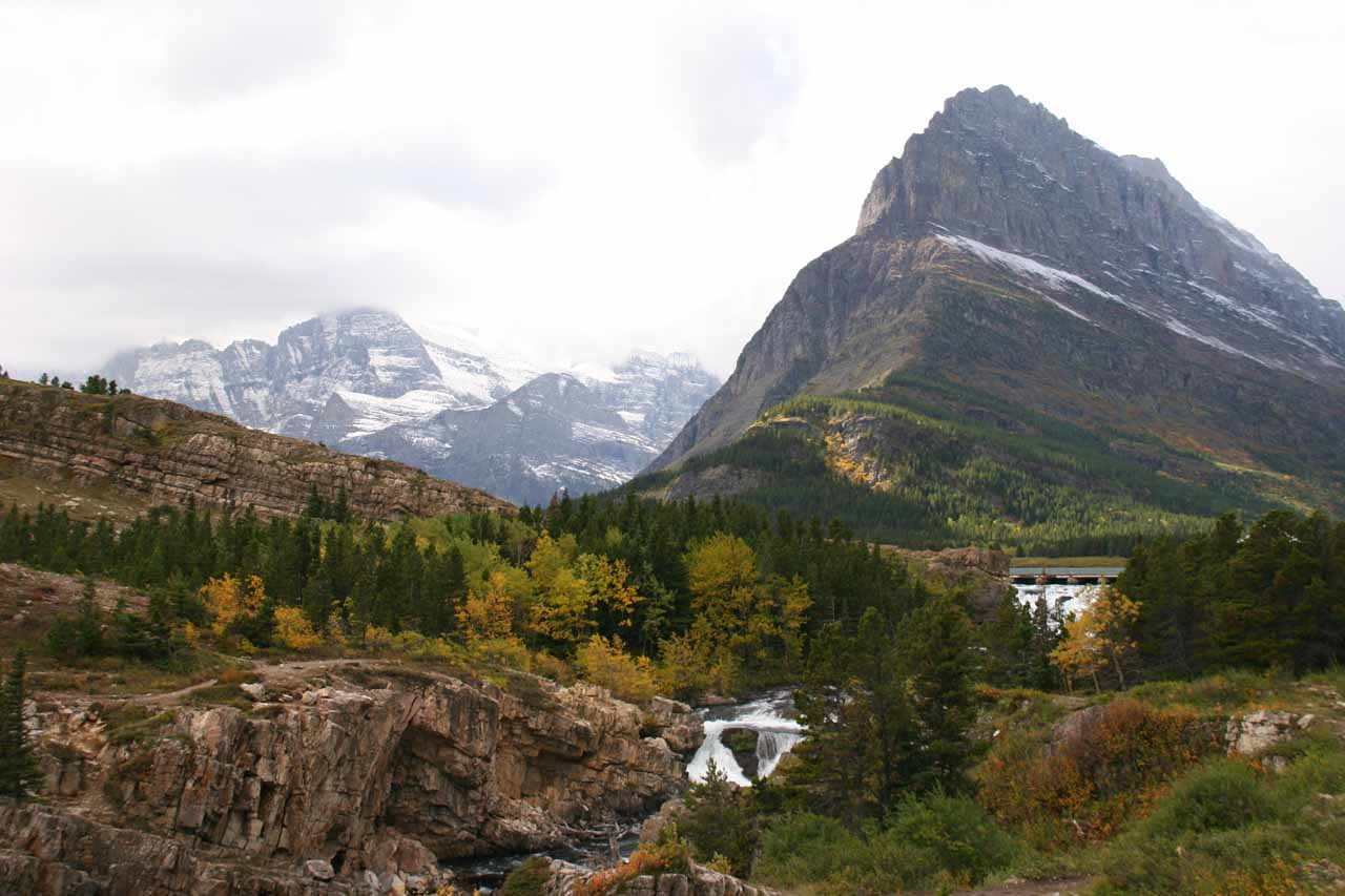 Looking over a cascade draining Swiftcurrent Lake with glacially shaped mountains in back