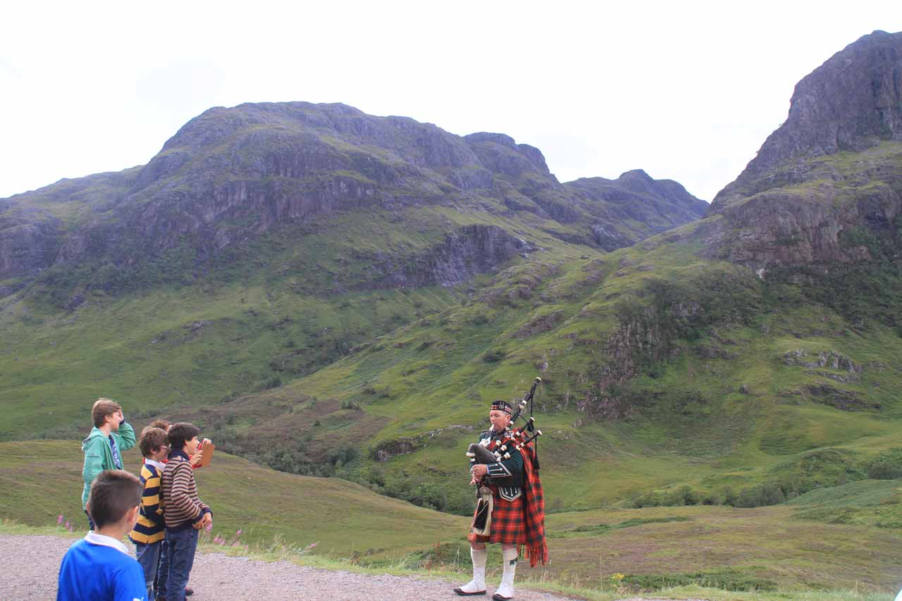 A lot of people listening to the Scottish bagpipe busker serenade at Glencoe Valley