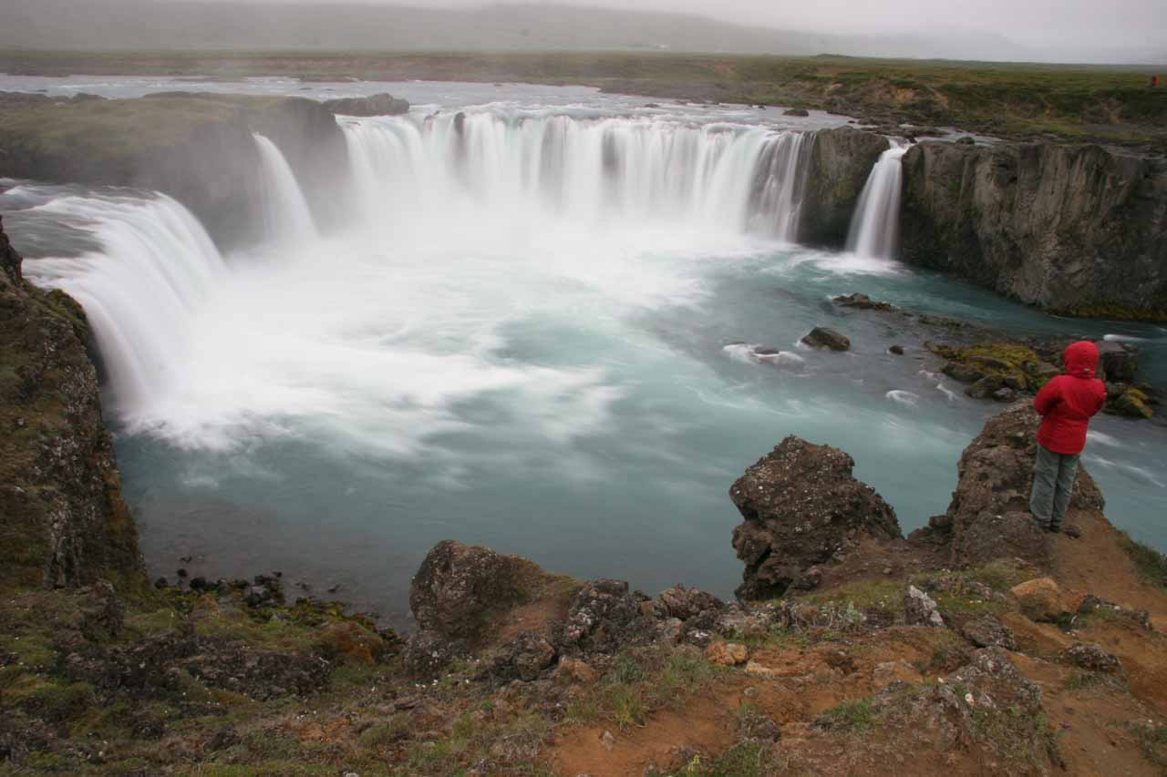 Julie precariously standing atop a bluff with a more top down view of Goðafoss from its east bank revealing its curved semi-horseshoe-shaped characteristic