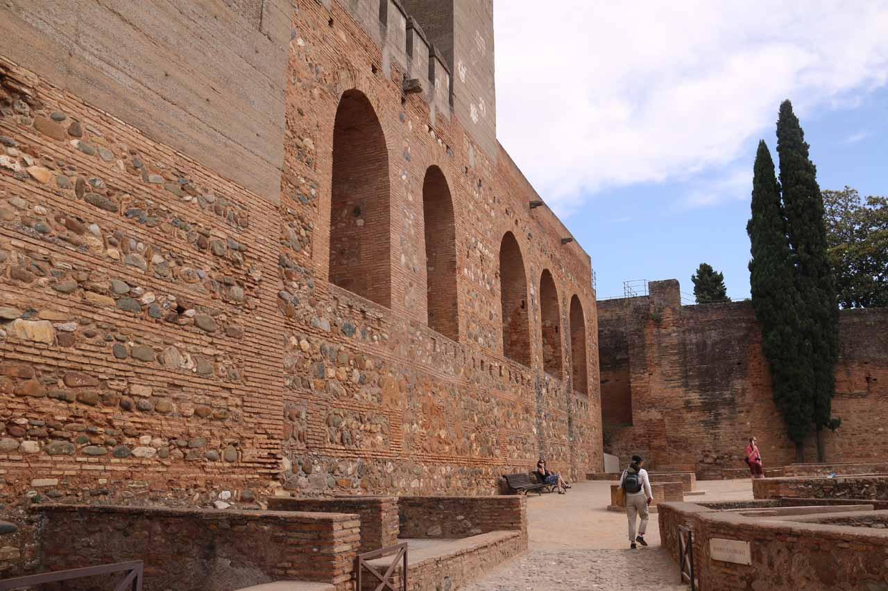Julie pushing forward walking beneath some imposing and maze-like parts of the Alcazaba