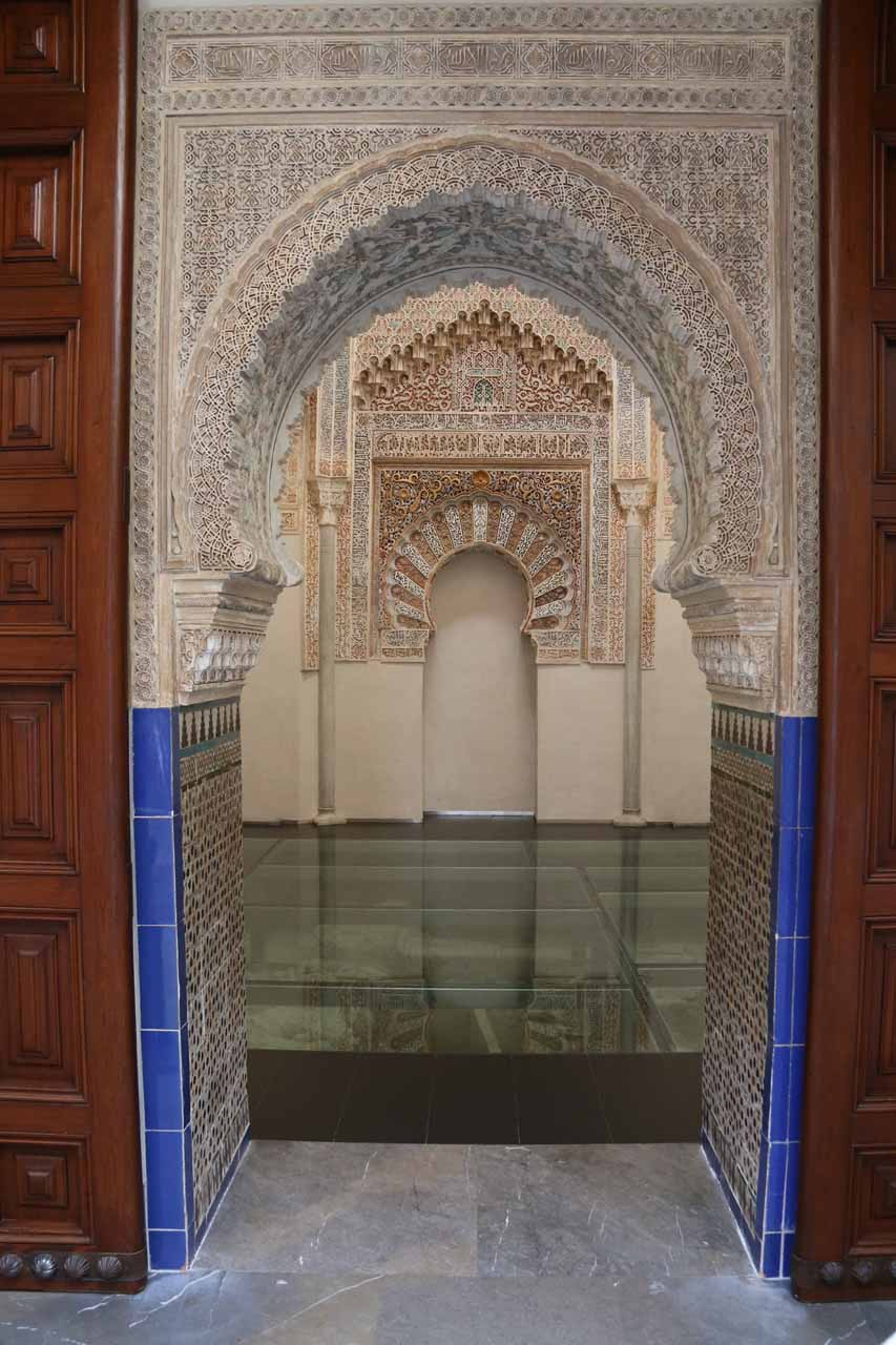Looking into an elaborate room through the Arabic arches at La Madraza