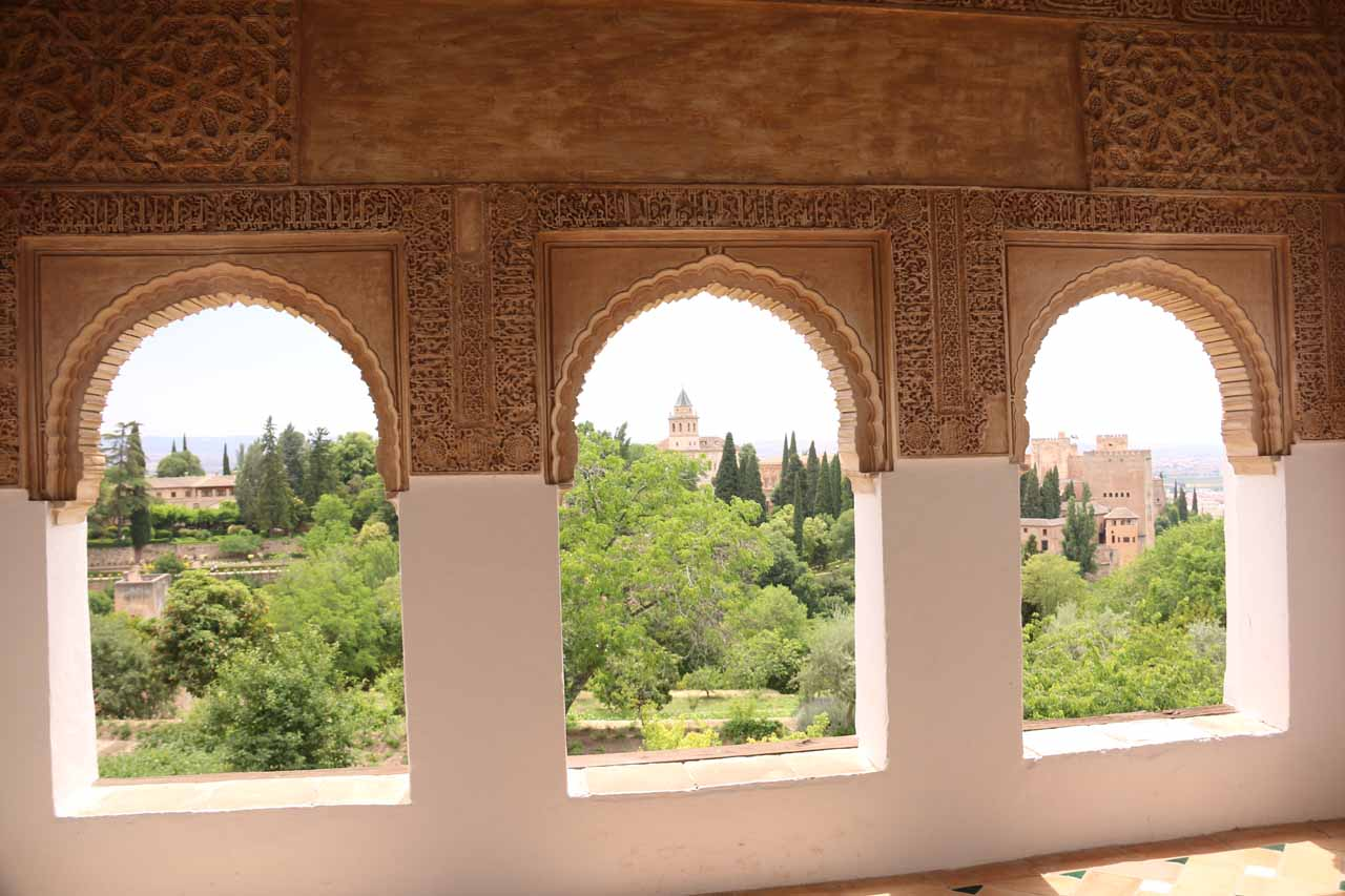 A trio of arched windows inside the Palace of the Generalife looking towards Alhambra