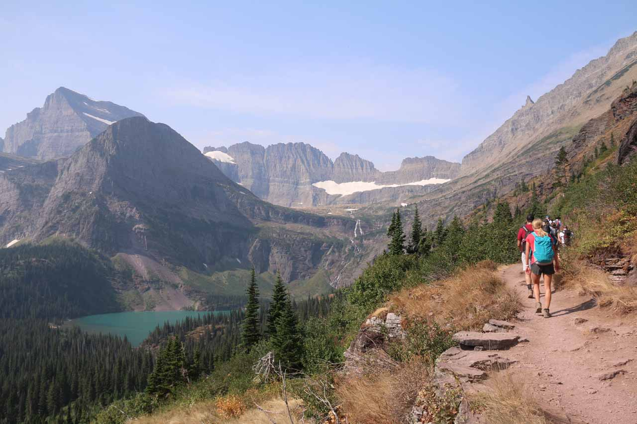 By the time the initial climb leveled out somewhat, the trail started providing distant views of Grinnell Lake and Grinnell Falls watched over by Angel Wing