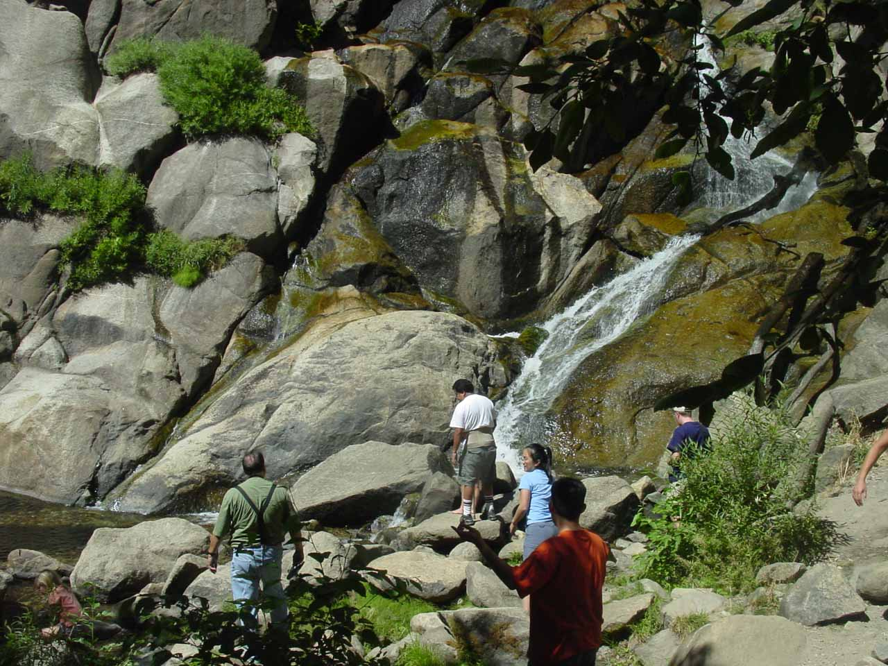 Some folks enjoying themselves by the plunge pool of Grizzly Falls in the late Summer