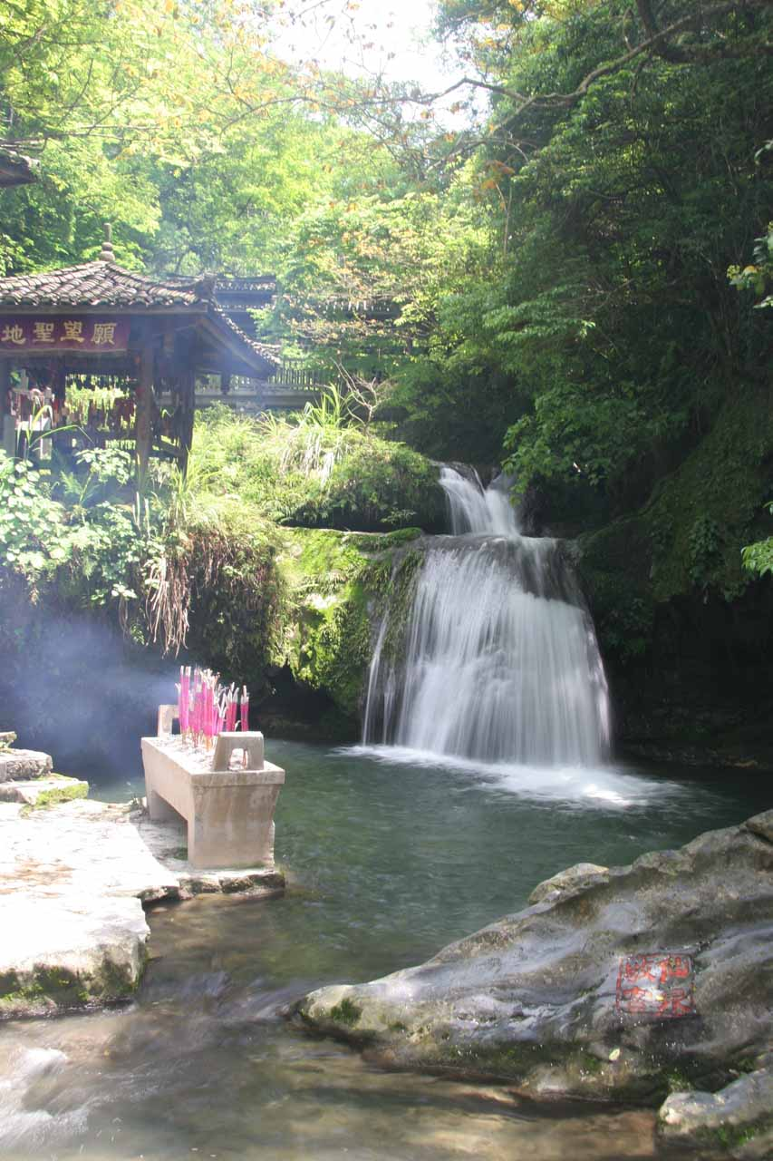 The last waterfall flanked by a shrine and some incense