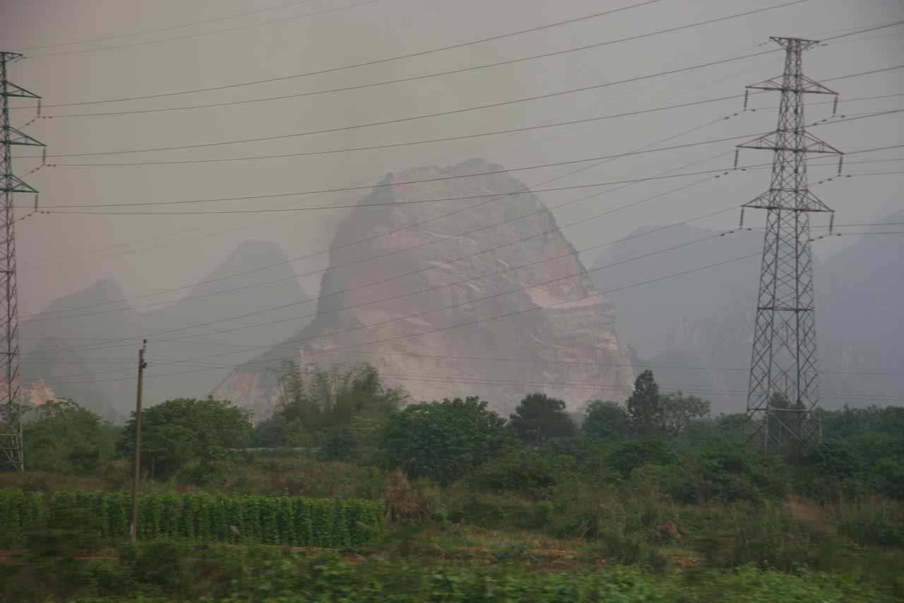 Hazy view looking back at a badly defaced karst mountain