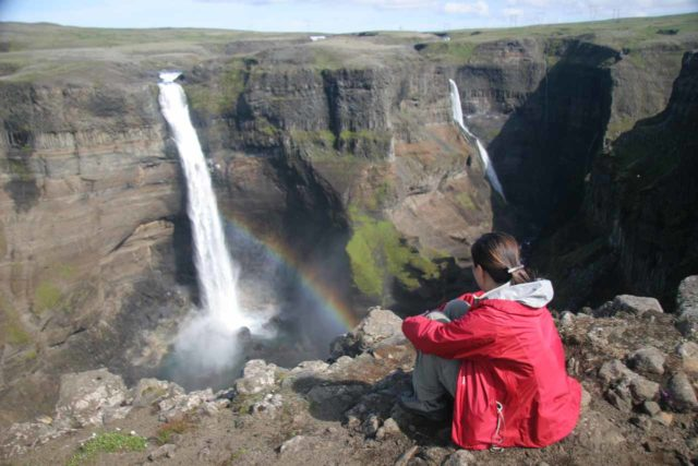 Haifoss_061_07082007 - Julie sitting down (to avoid falling over the cliff) admiring the surreal scene of Háifoss and Granni with a rainbow