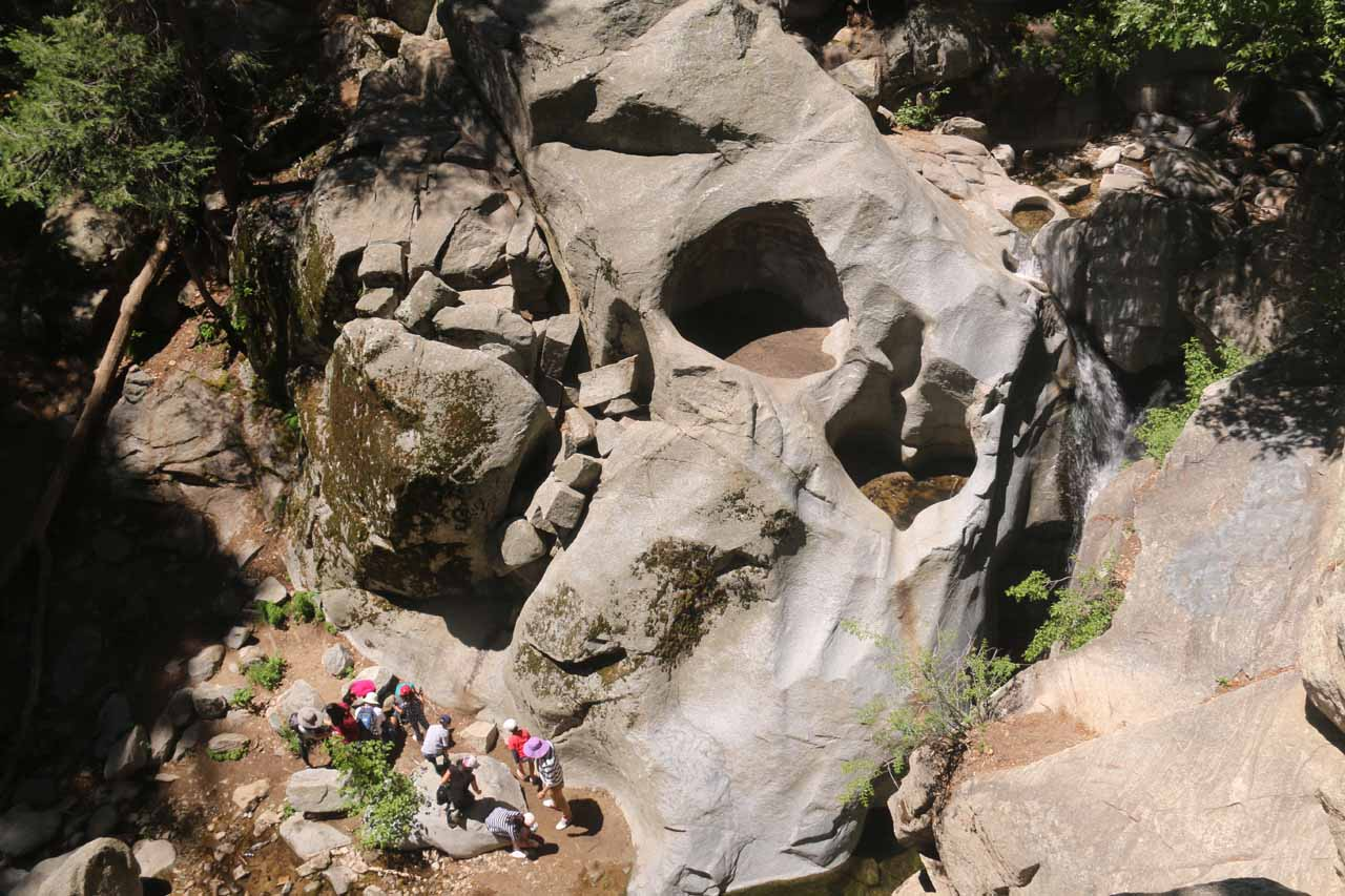 Looking down at some people at the base of Heart Rock Falls in context with the Heart Rock and waterfall themselves