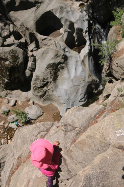 Heart_Rock_Falls_17_044_05202017 - Context of Tahia looking precariously towards the heart-shaped depression of Heart Rock Falls. Note the person in blue looking tiny further below, which illustrates how high up she was