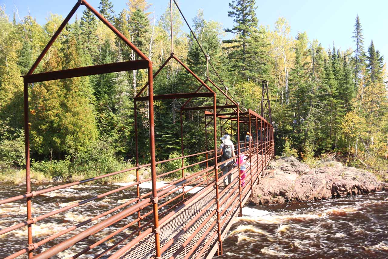 Julie and Tahia crossing the swinging bridge above the Baptism River