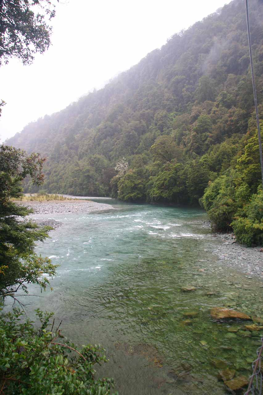Looking over the clear Hollyford River while crossing the swinging bridge