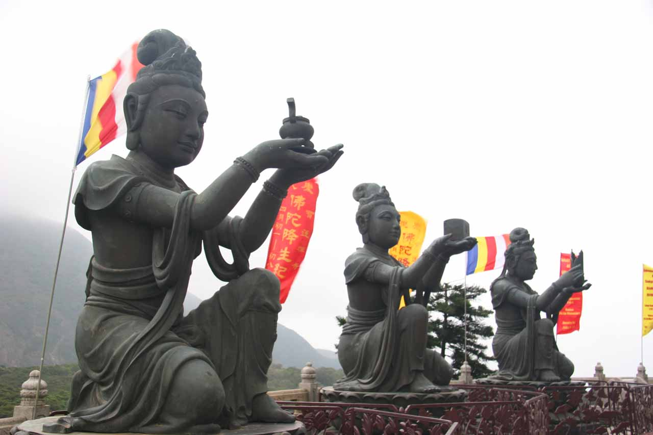 Smaller statues offering up something to the Big Buddha