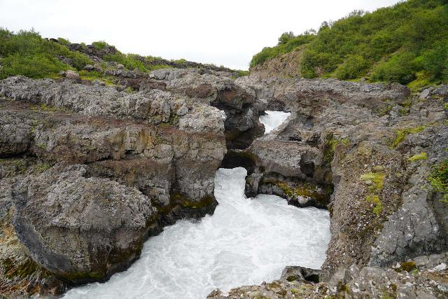 Hraunfossar_111_08182021 - Looking at the lone natural bridge still standing across the turbulent rapids squeezed in by the Hallmundarhraun Lava Field at the Barnafoss Waterfall