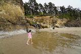 Hug_Pt_058_06232021 - Tahia walking across the drainage of the waterfall at Hug Point Beach