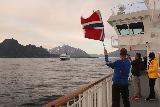 Hurtigruten_day4_427_07022019 - Eschild waving a Norwegian flag towards the MS Trollfjord as he knew his son was aboard that ship