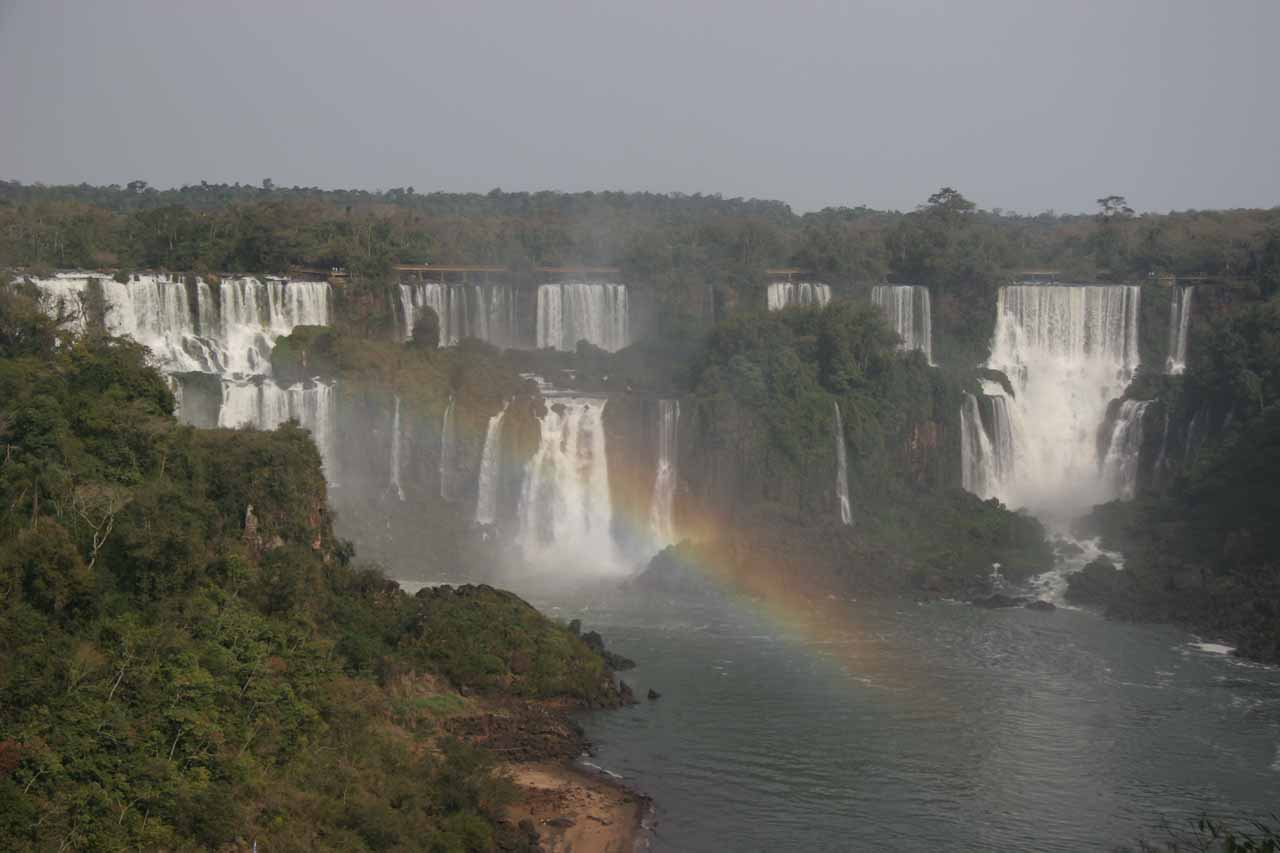 Rainbow cutting across the view of some waterfalls in the Argentina side