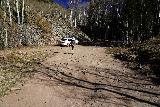 Judd_Falls_034_10162020 - Julie approaching some sedan that actually chanced going up the road to the Copper Creek Trailhead. I'd bet he had to have sustained some undercarriage scraping to even get this far