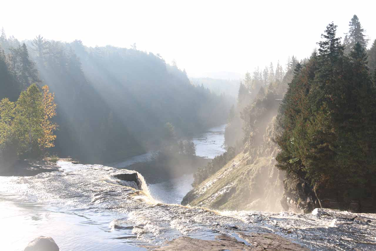 Looking downstream over the top of Kakabeka Falls from the bridge against the morning sun