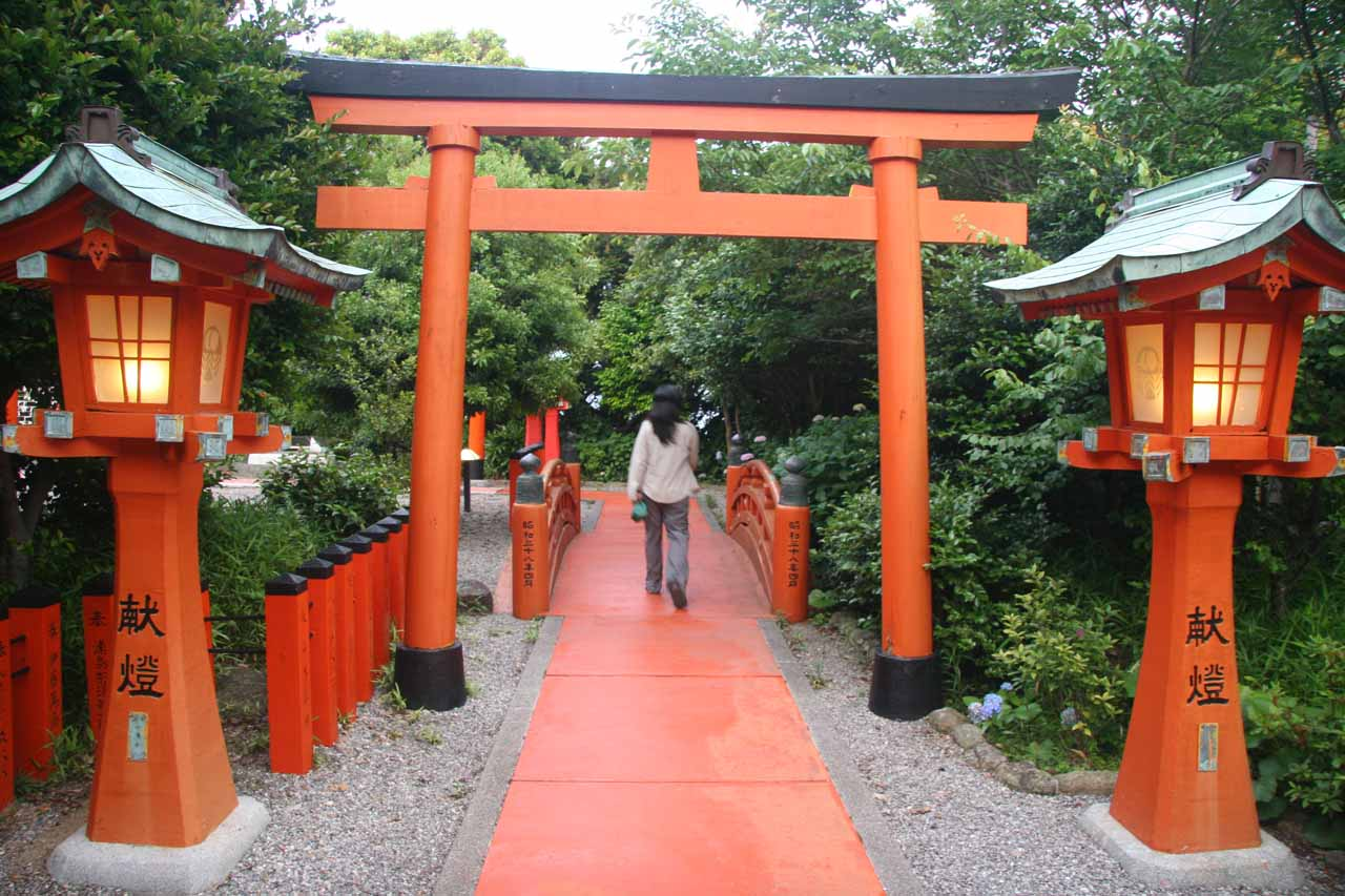 Julie going beneath a torii and entering an attractive garden area atop Hotel Urashima