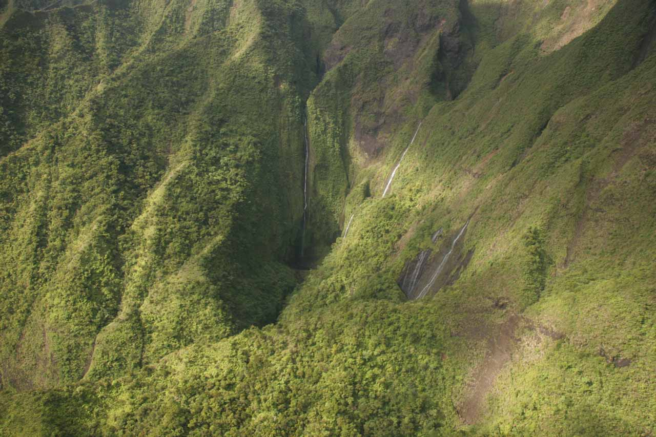 Waterfalls coming down into a lush area off the beaten path of Kauai's mountains